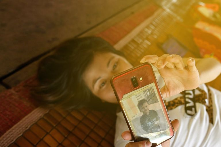 A woman lays on the ground while using her smartphone