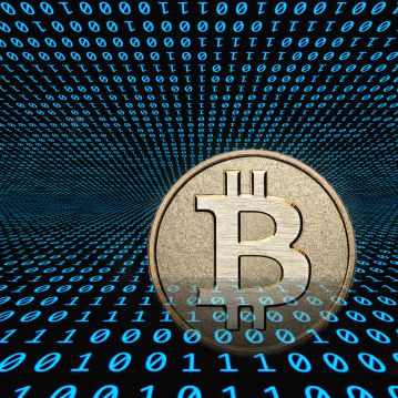 A physical representation of a Bitcoin with binary code behind