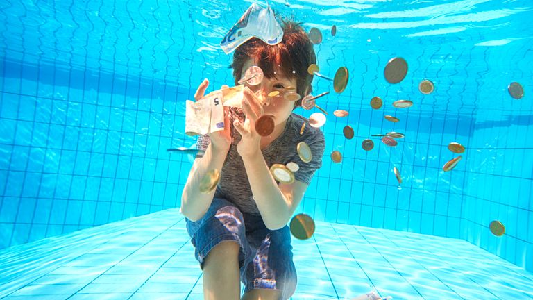 Young boy swimming in a pool with money