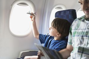 A child on an airplane playing with a toy plane with his father sitting next to him.