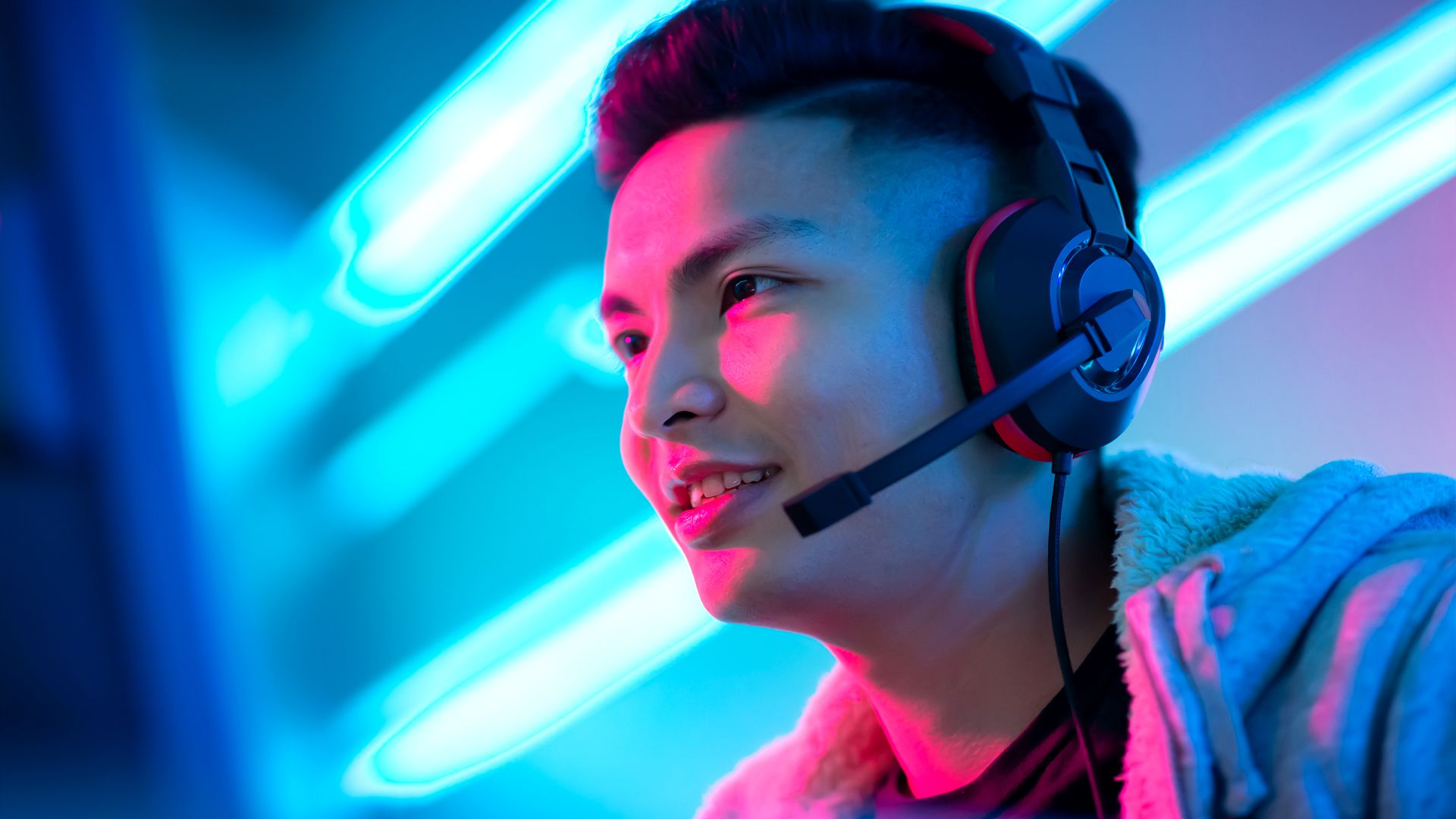 A young man playing a video game while wearing a headset with a microphone and headphones.