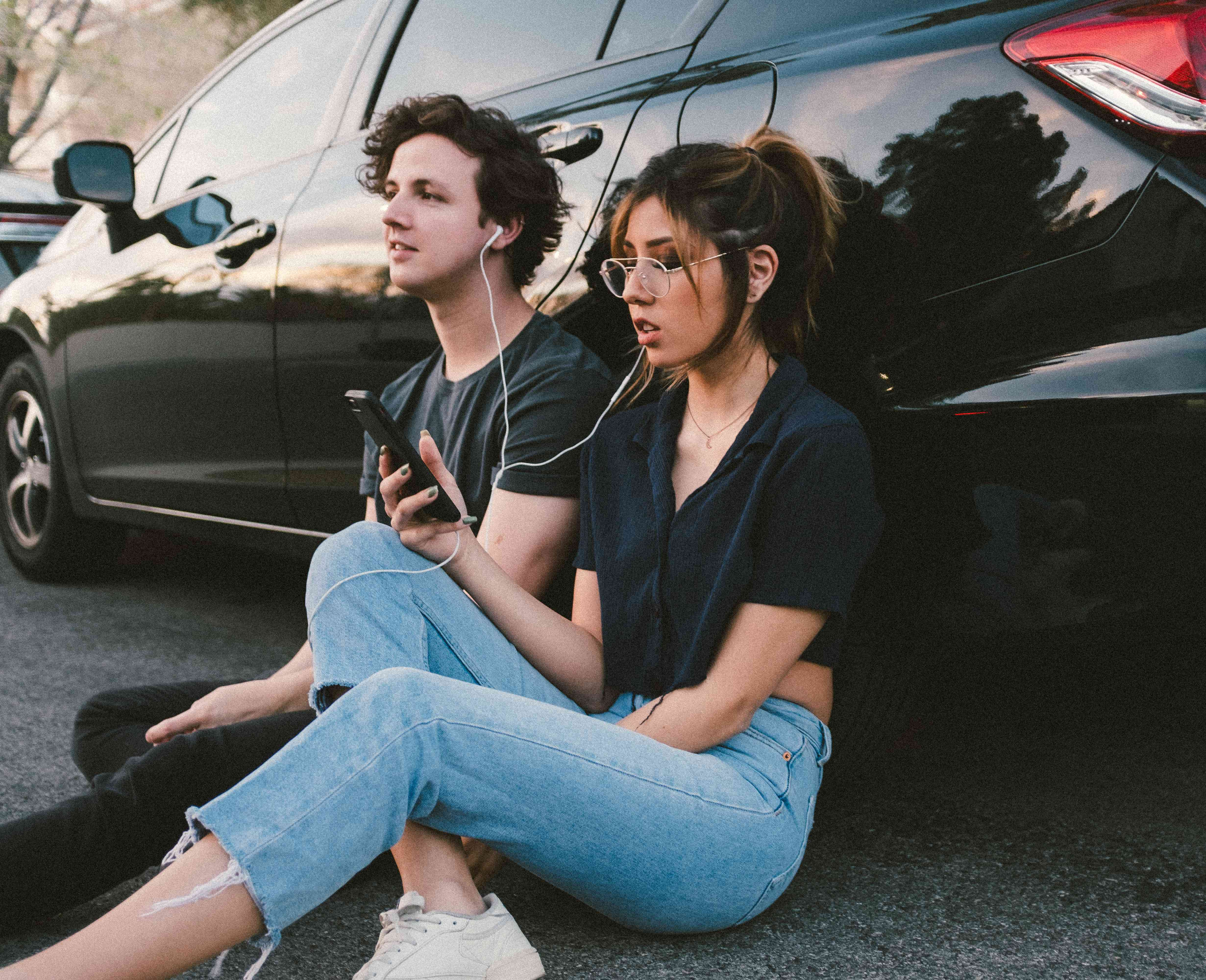 Friends sitting on the ground, leaned against a vehicle, sharing music from a smartphone with wired headphones.