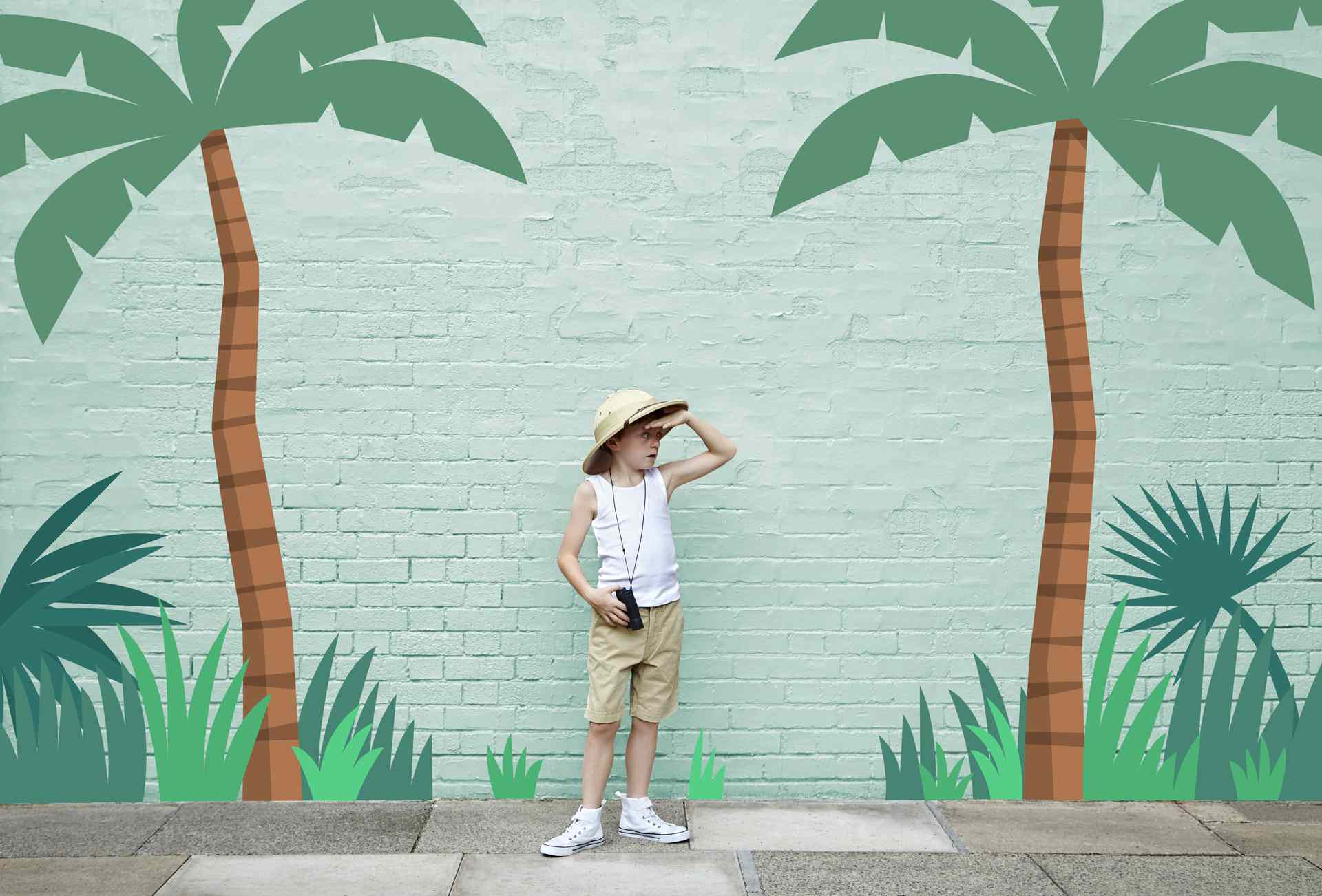 A boy in a safari outfit standing in front of a jungle adventure painting.