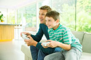 Parent and child playing video games in living room