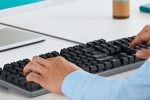 Man typing on Logitech K840 keyboard
