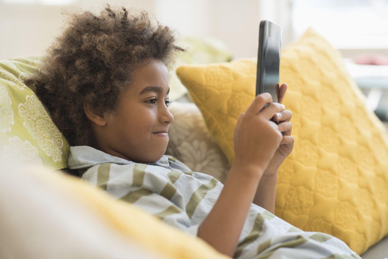 Boy using digital tablet in living room