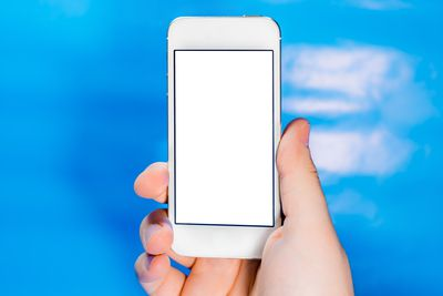Cropped Hand Holding Smart Phone Against Blue Background