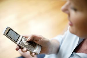 An image of a woman using a flip phone.