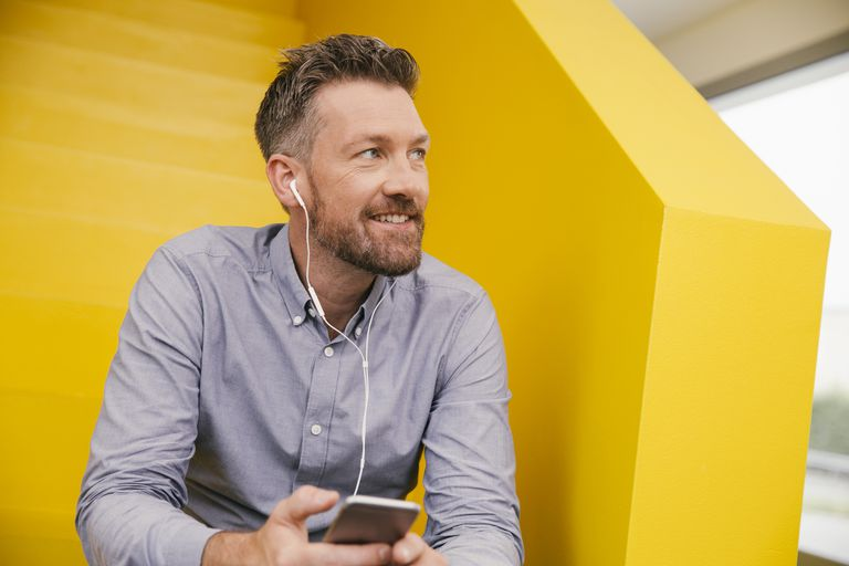 Portrait of smiling mature man hearing music with smartphone and earphones sitting on yellow stairs