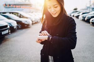 A woman standing in a car park looking down at her smartwatch
