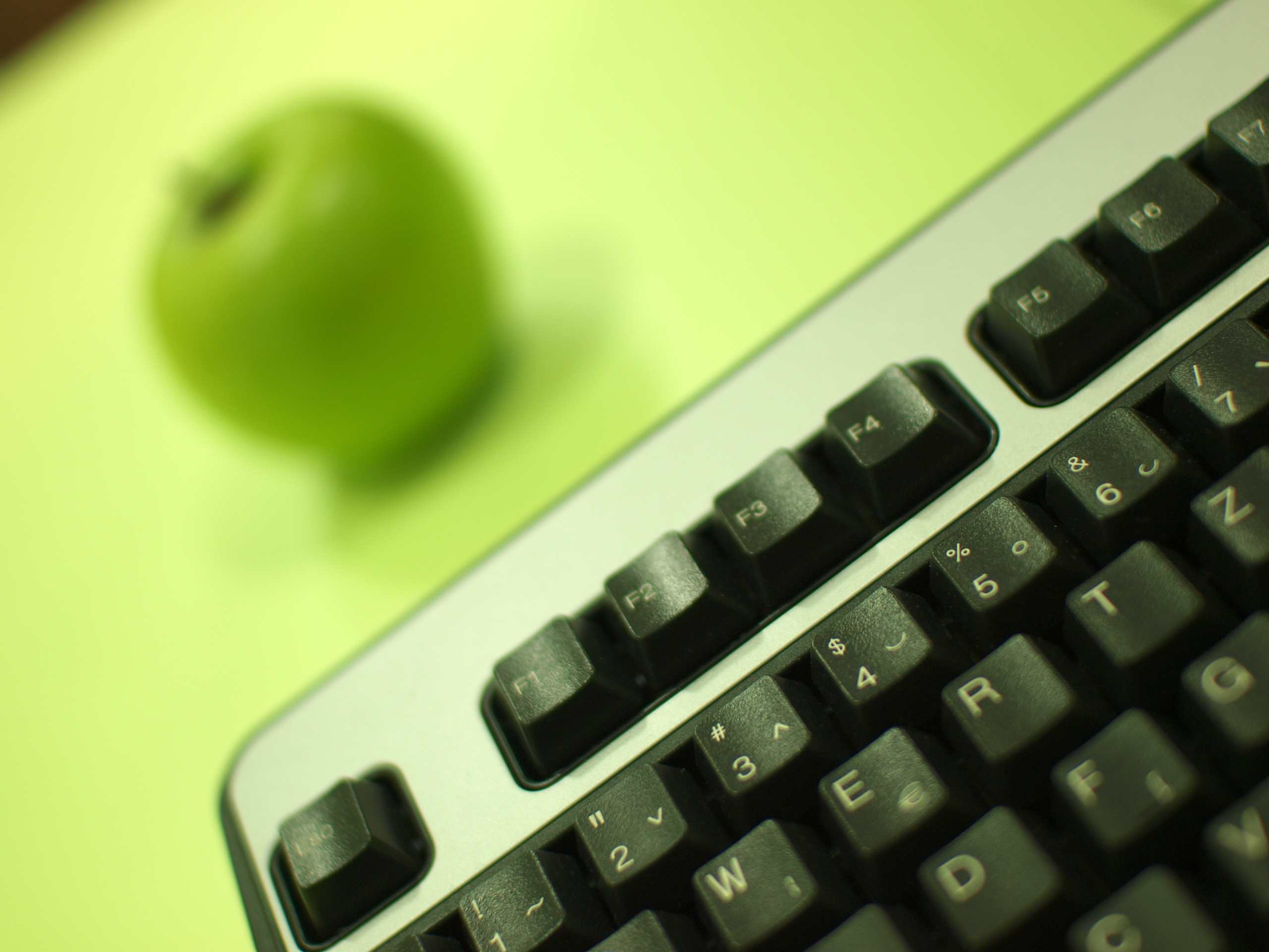 Green apple and computer keyboard