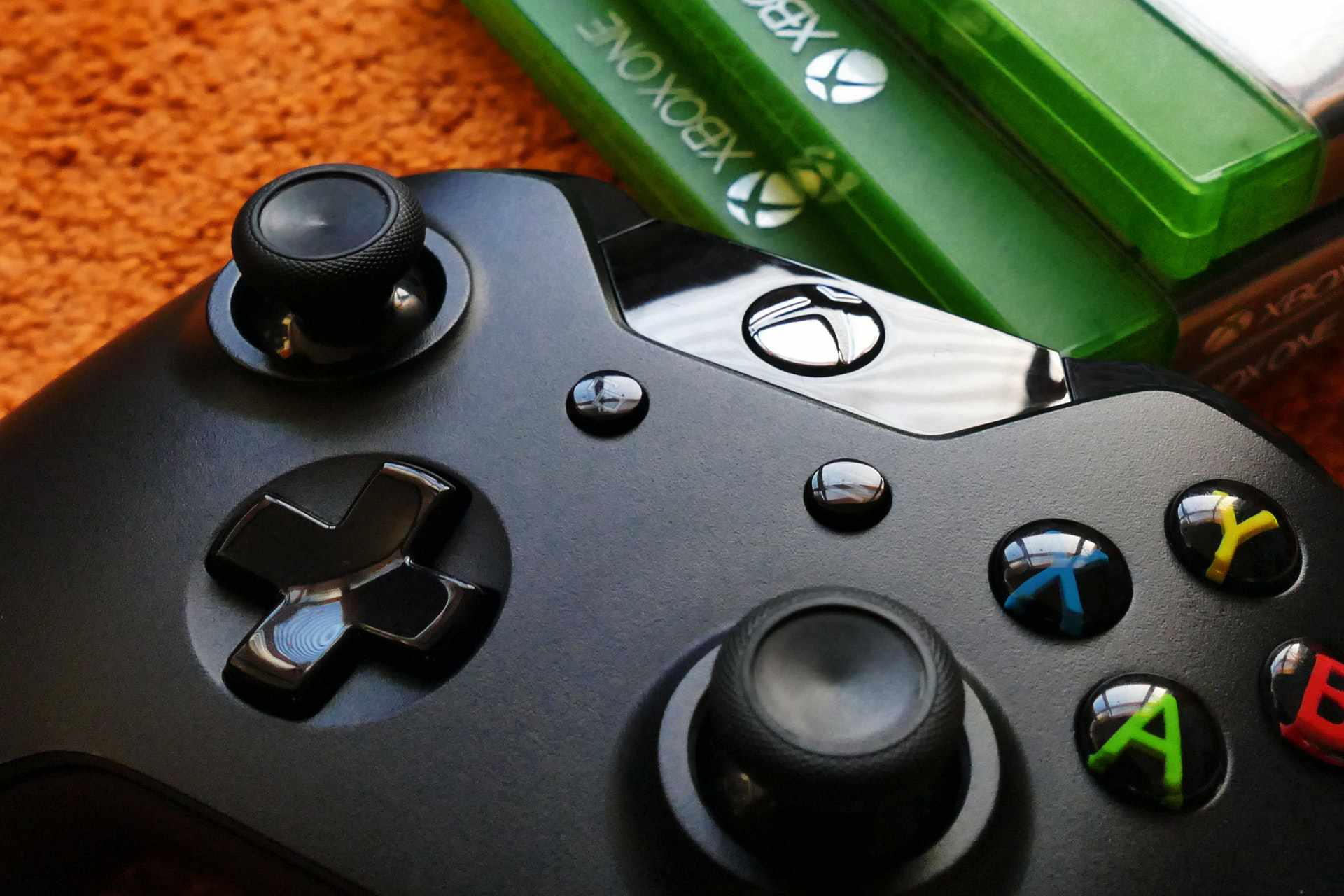 An Xbox controller with games in the background.