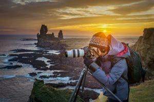 Woman taking a coastline photo with DSLA camera