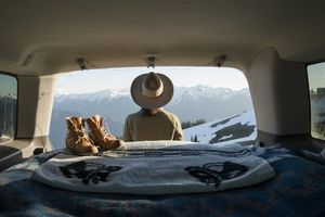 Hiker sitting in car in front of snow-capped mountains