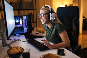 A woman smiling at a desk looking at a PC monitor screen