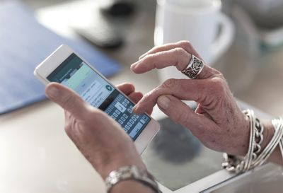Hands of an elderly woman typing on her smartphone.