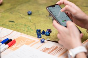 Someone using the smartphone during a role-playing game of Dungeons & Dragons, map and dice in the background.
