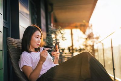 A woman sitting on her porch looking at her smartphone while holding a credit card in her other hand