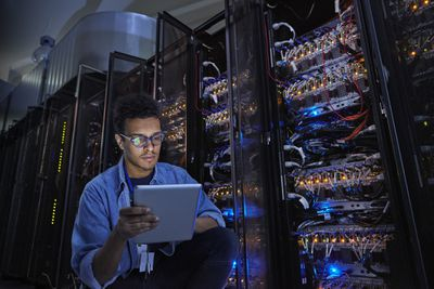Young system administrator in server racks