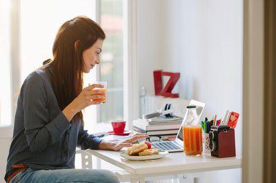 Home-based freelancer using laptop while breakfasting