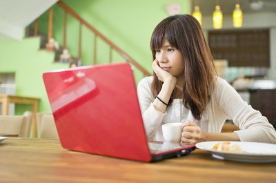Girl with teacup looking into red laptop