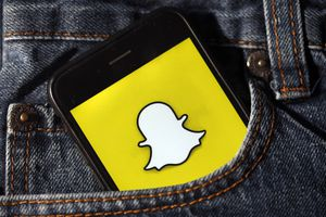 The Snapchat logo on a smartphone in someone's pocket.