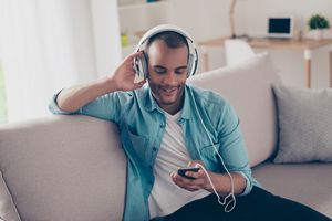 Young man listening to songs on his iPhone with headphones.