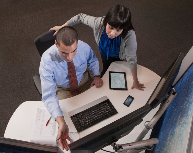 Man and woman looking at monitor with tablet on desk