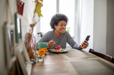 Woman eating breakfast and having video call.