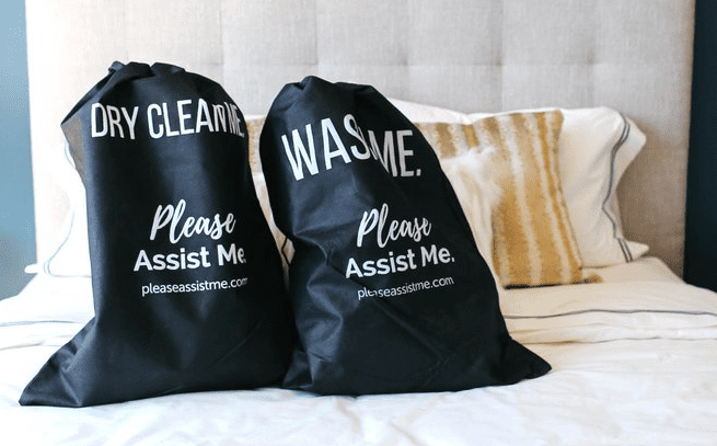 A pair of black Please Assist Me laundry bags resting on a bed