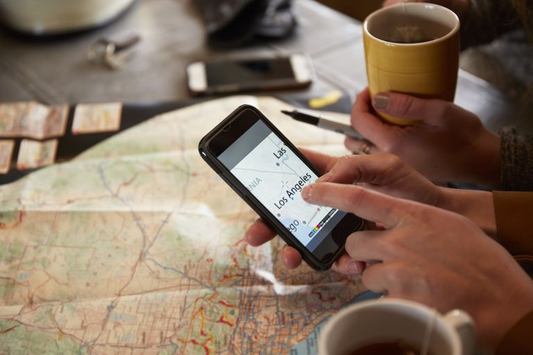 A person is holding an iPhone next to a traditional map. The iPhone displays the Maps app.
