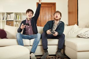 Two young men sitting on a sofa holding games controllers. One is cheering while the other looks frustrated