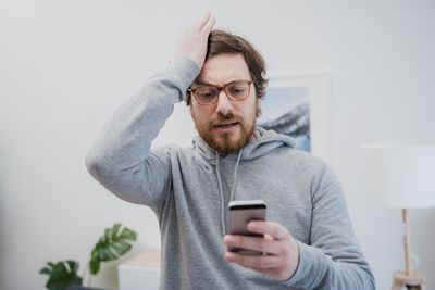 male reading bad news on his smartphone