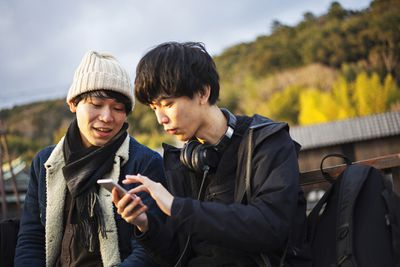 A couple standing outside looking at a smartphone
