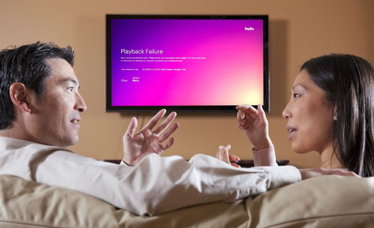 hulu playback failure message on tv behind couple arguing