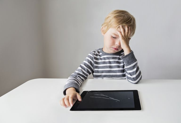 Boy looking at broken digital tablet