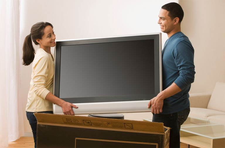Hispanic couple carrying new television