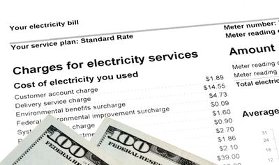 Sample electric bill with $100 dollar bills on top.