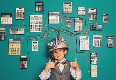 Young child wearing a makeshift helmet connected by wires to many calculators.
