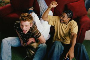 Two boys are cheering while holding games controller