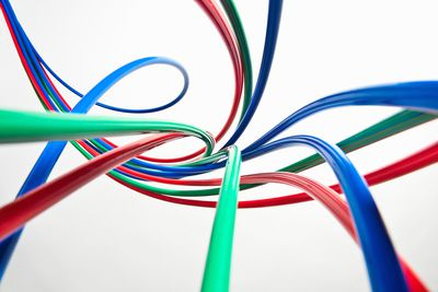 Red, green and blue plastic tubing on white background.