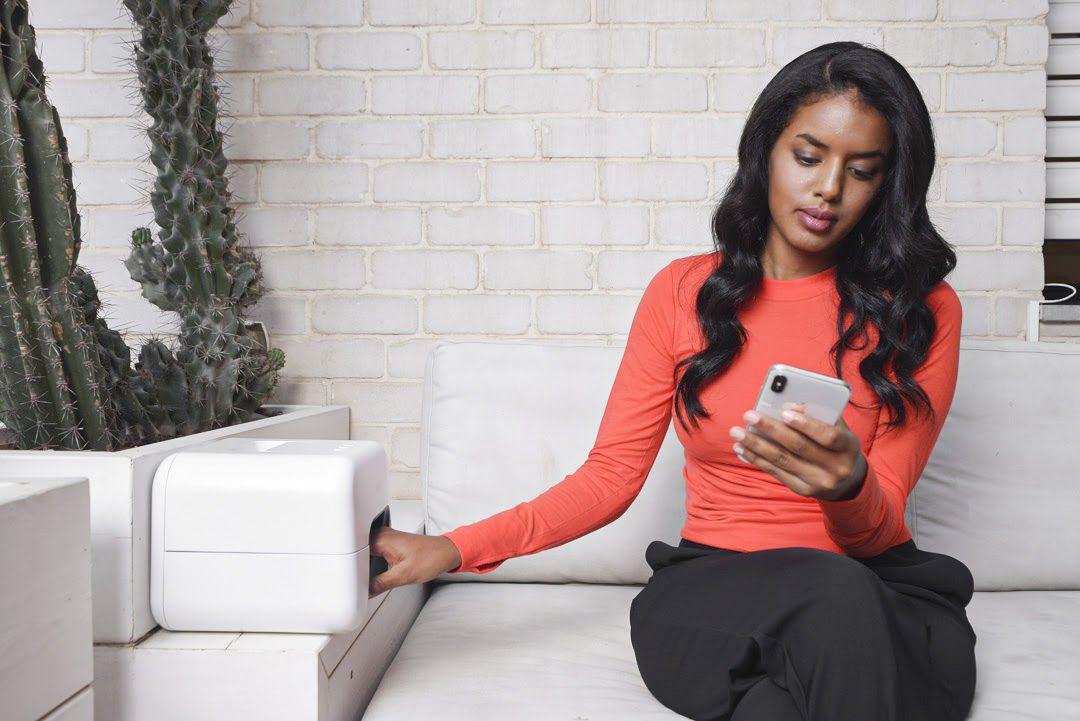 Woman using Nimble's AI nail machine while using her phone