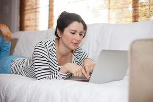 Woman laying on sofa using laptop computer