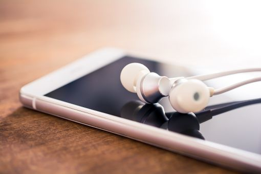 White earbuds lying on top of an iPhone on a table