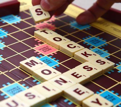 A hand places a letter tile on a Scrabble board