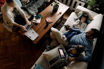 A family gathered in the living room all looking at different devices