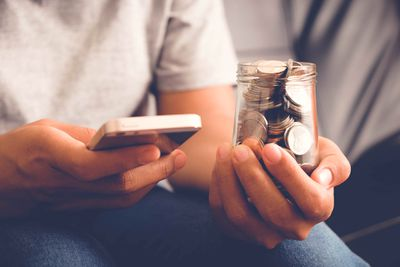 A man holding an iPhone in one hand and a jar of coins in the other.