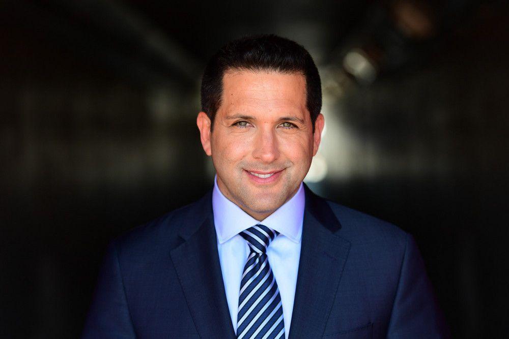 A headshot of ESPN reporter Adam Schefter