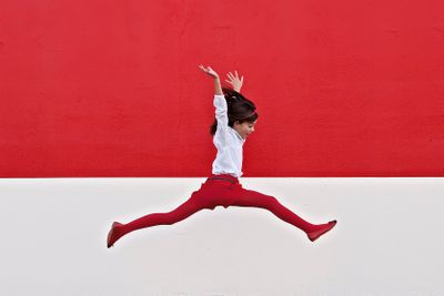 Girl jumping in air at red wall