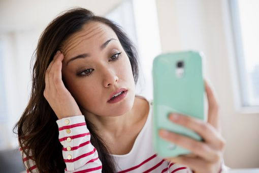 A stressed woman looking at her smartphone screen.